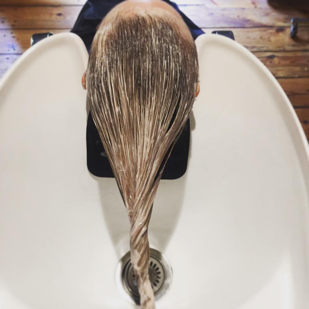 Treatment in progress long blonde hair in basin at ESHK hair salon in Shoreditch