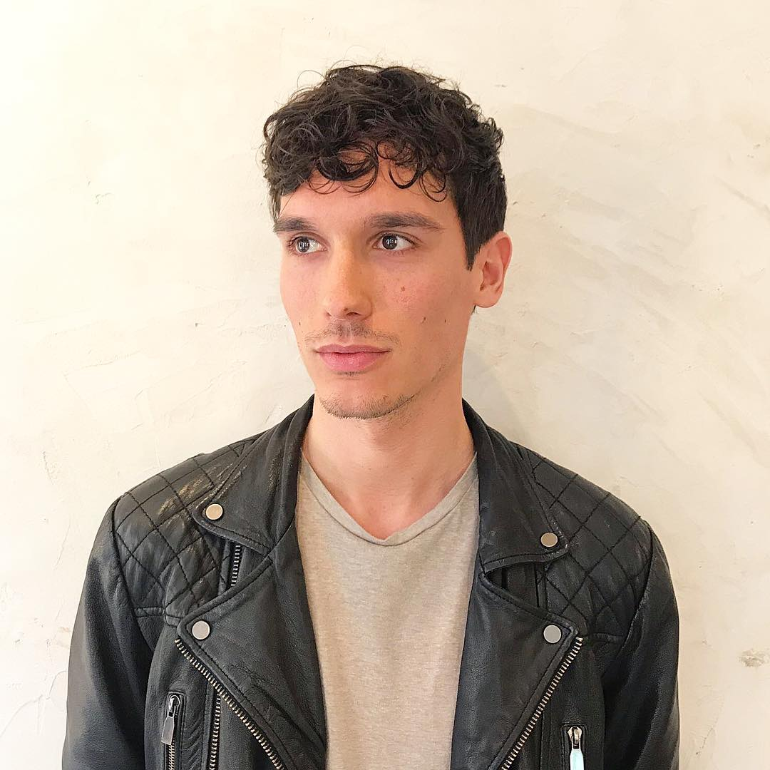short black curls gents haircut leather jacket